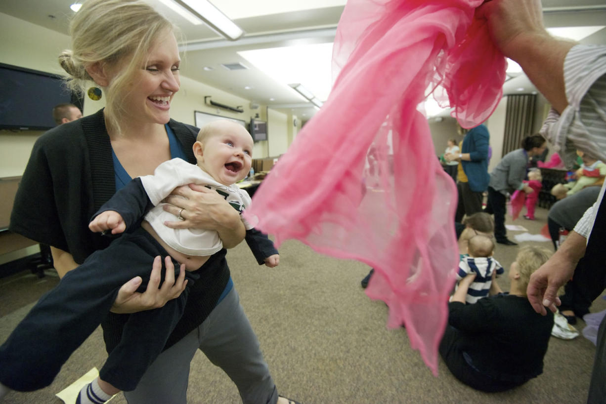 """Heather Stuart, left, and her 7-month-old son, Obadiah, laugh as dad Steve Stuart, a Clark County commissioner, playfully waves a pink scarf during the """"Love, Talk, Play"""" event Thursday at the Center for Community Health in Vancouver."""