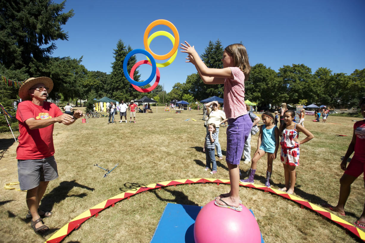 Ellie Johnson, 8, plays a hoop game with Bill Hewitt of Circus Cascadia while balancing on a ball at John Ball Park during the Sunday Streets Alive event.