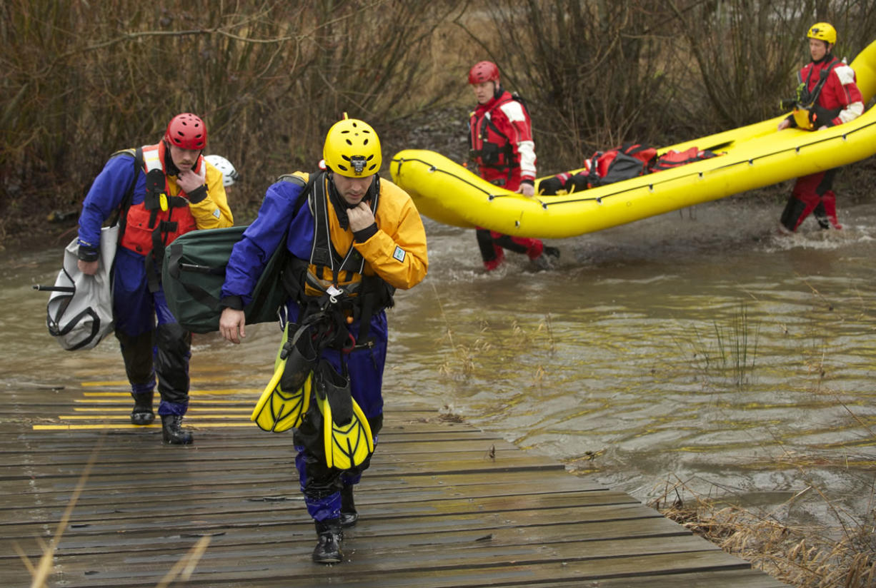 Rescue team members pull out of Salmon Creek after retrieving three young brothers whose kayak had overturned in the water and two members of a state prison work crew who went to the boys' aid.
