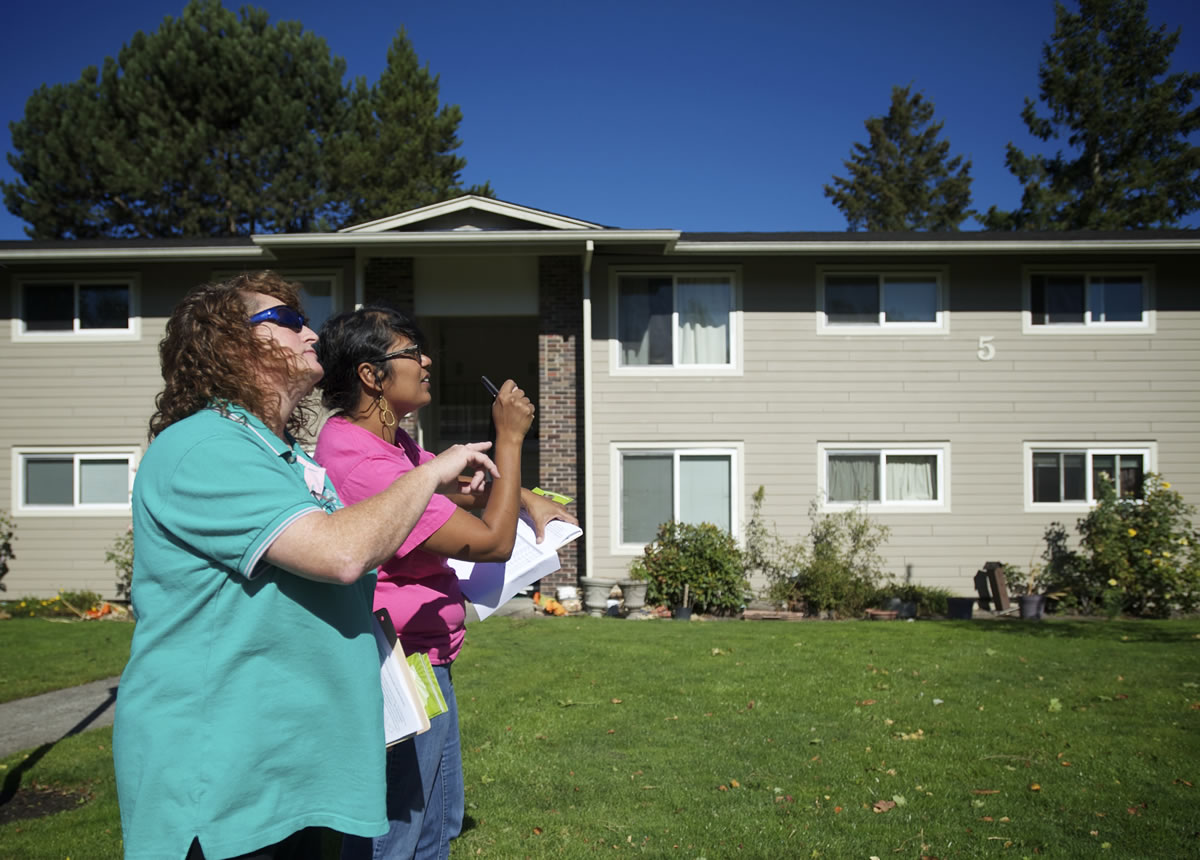 Same-sex marriage advocate Amy Wells, left, 51, of Vancouver, and Basic Rights Oregon Organizing Director Raahi Reddy, 40, of Portland, look for specific addresses inside an apartment complex in Hazel Dell as they canvass on Saturday.