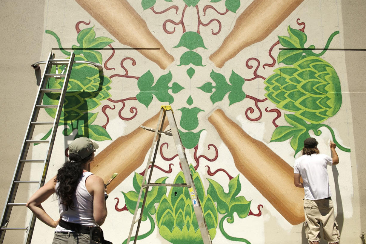 """Tamra Davisson, left, looks over the progress of a mural she and Jason Galles, right, are painting on Wednesday in downtown Vancouver. """"They're great impact art,"""" Davisson said."""