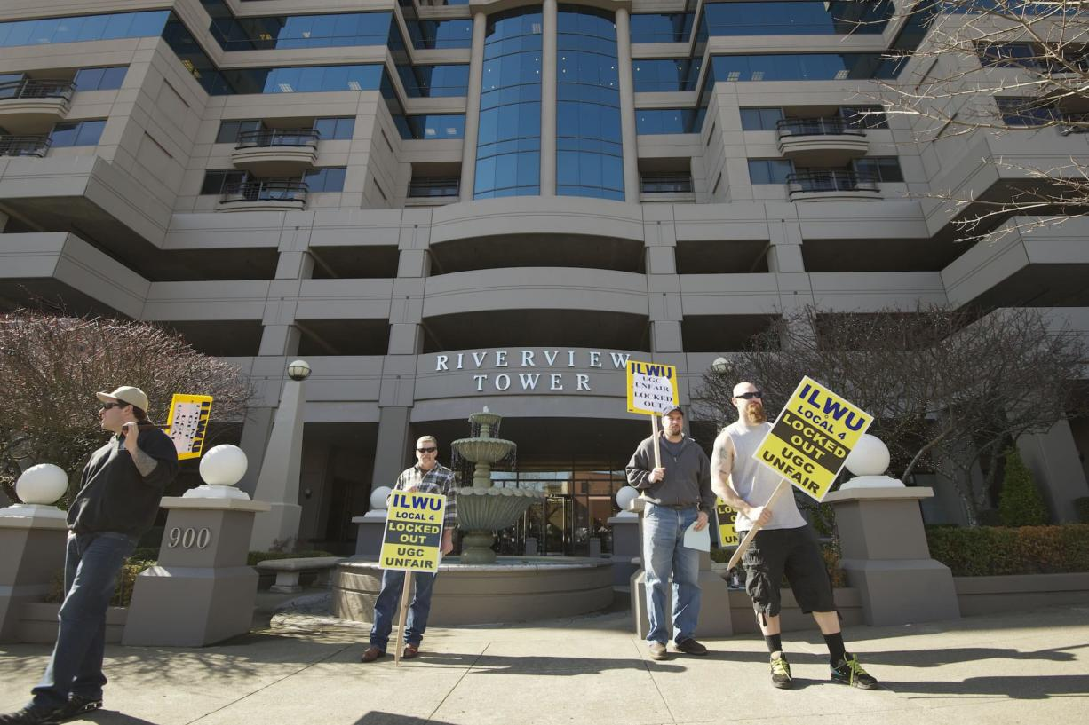 Picketers carry signs Thursday outside Riverview Tower in downtown Vancouver, where United Grain Corp.  has an office. The company locked out 44 International Longshore and Warehouse workers on Feb.