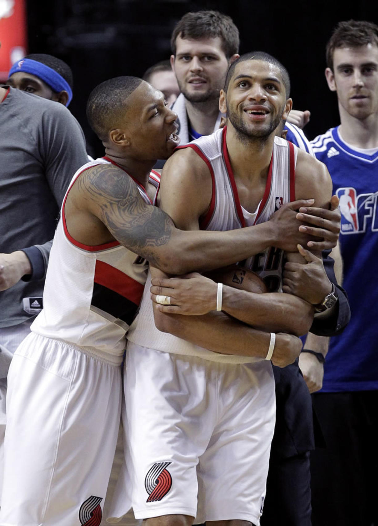 Portland Trail Blazers guard Damian Lillard, left, hugs teammate Nicolas Batum after winning an NBA basketball game against the Los Angeles Clippers in Portland, Ore., Saturday, Jan. 26, 2013.  Both players scored 20 points each as the Trail Blazers won 101-100.