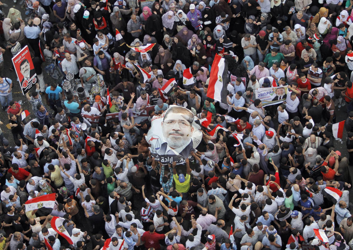 Egyptians carry a poster showing newly elected President Mohammed Morsi in Tahrir Square in Cairo, Egypt, on Sunday.