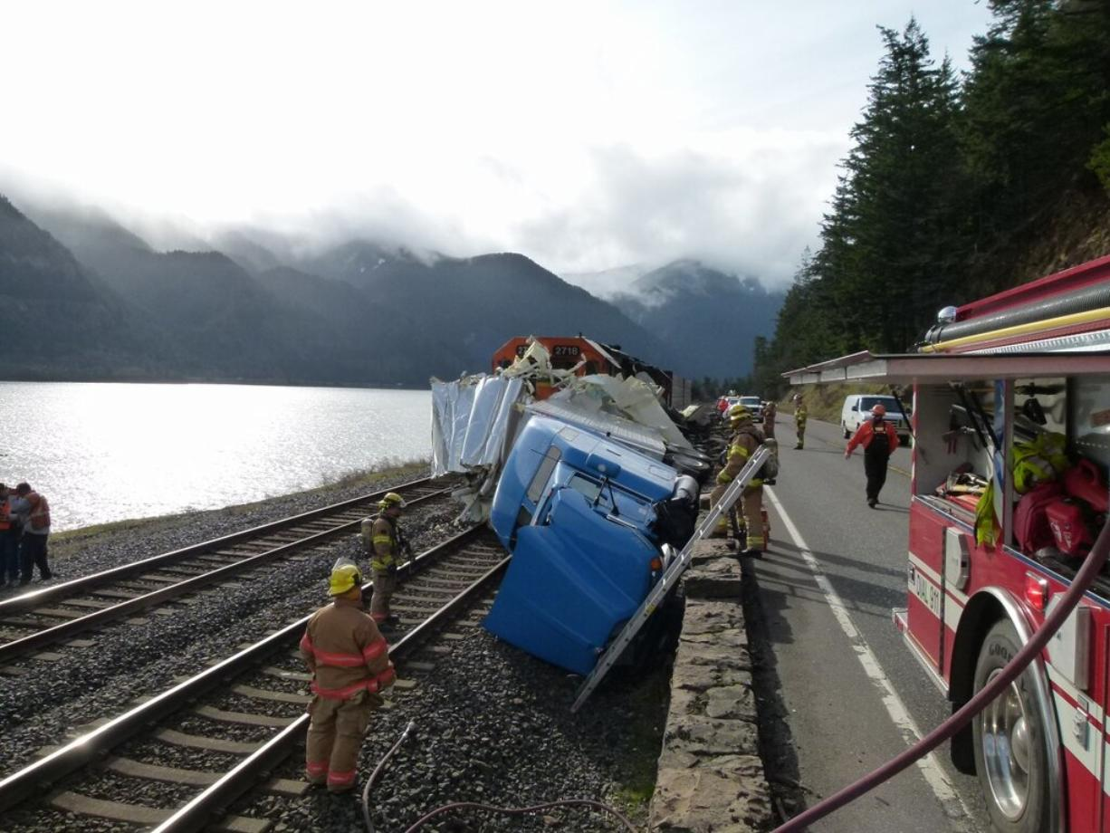 Firefighters help at the scene of a truck-train wreck in the Columbia River Gorge on Thursday afternoon.