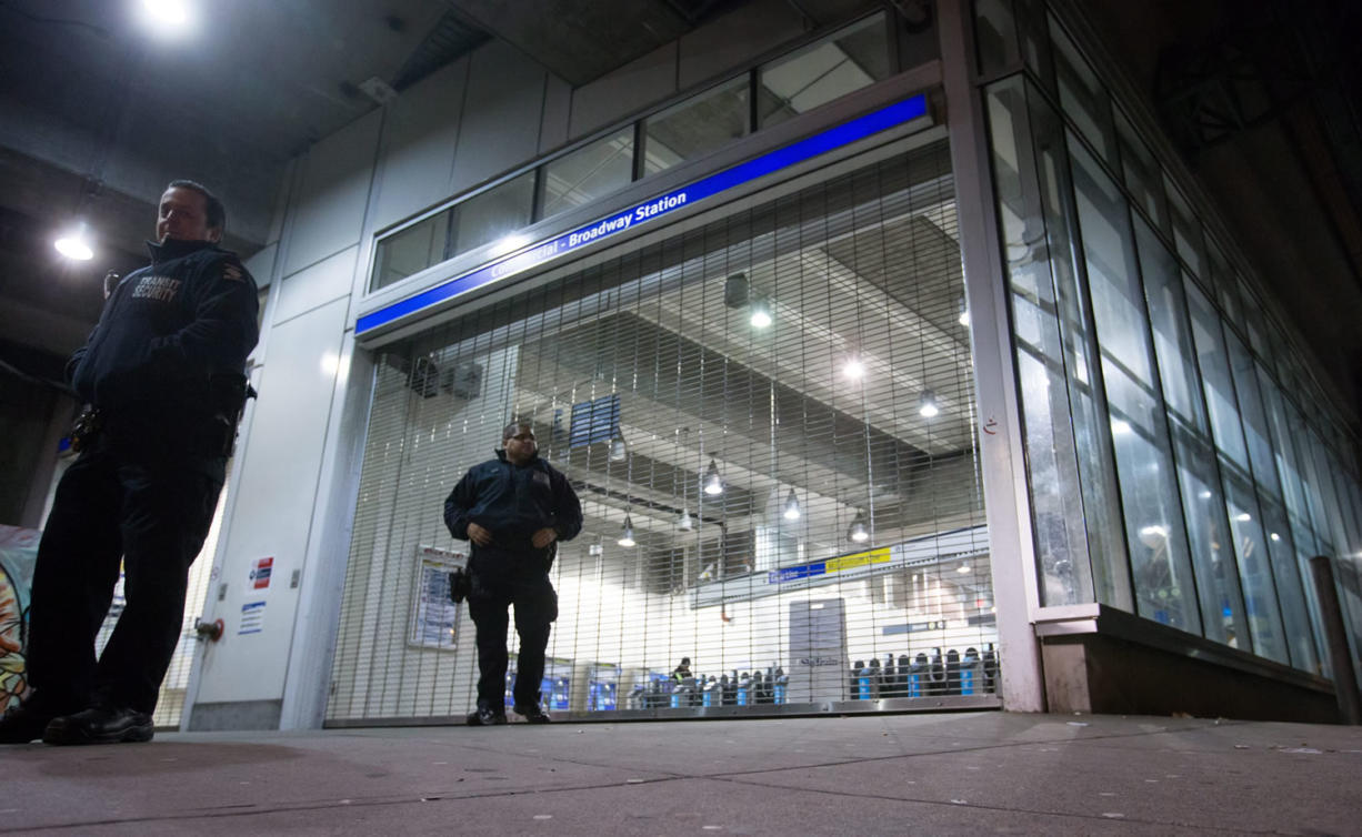 Transit security officers stand outside the Commercial-Broadway Skytrain station after the commuter train system was shut down to check for any possible damage to elevated guideways in Vancouver, B.C., early Wednesday after an earthquake struck off the western coast late Tuesday night. The moderate quake struck at 11:39 p.m. local time Tuesday about 20 kilometres north of Victoria and was felt across much of southern British Columbia. (Darryl Dyck/The Canadian Press via AP) MANDATORY CREDIT