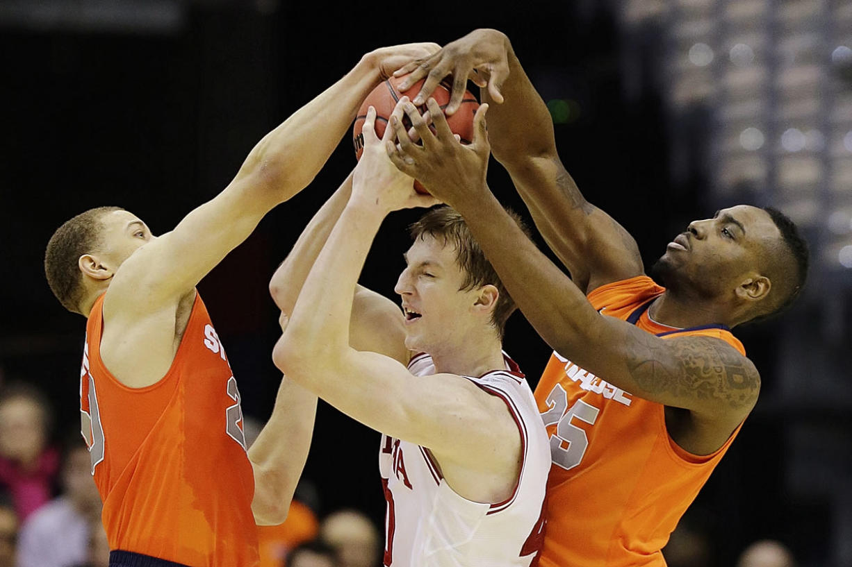 Indiana forward Cody Zeller (40) is trapped between Syracuse guard Brandon Trich, left, and forward Rakeem Christmas (25) during the first half of an East Regional semifinal in the NCAA college basketball tournament, Thursday, March 28, 2013, in Washington.
