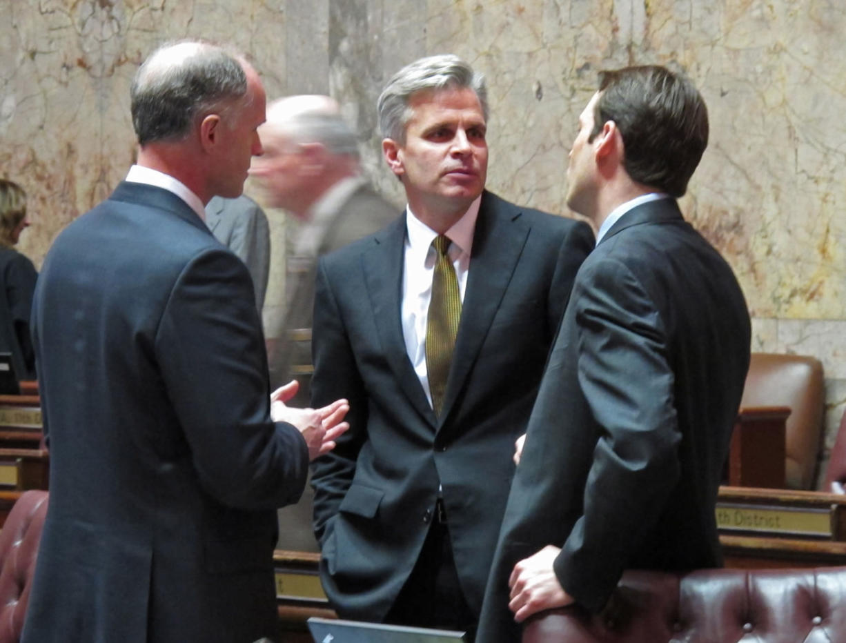 Republican Sen. Steve Litzow, center, talks with Majority Coalition Caucus leader Rodney Tom, left, and Democratic Sen. Andy Billig, right, on the state Senate floor on Wednesday in Olympia.