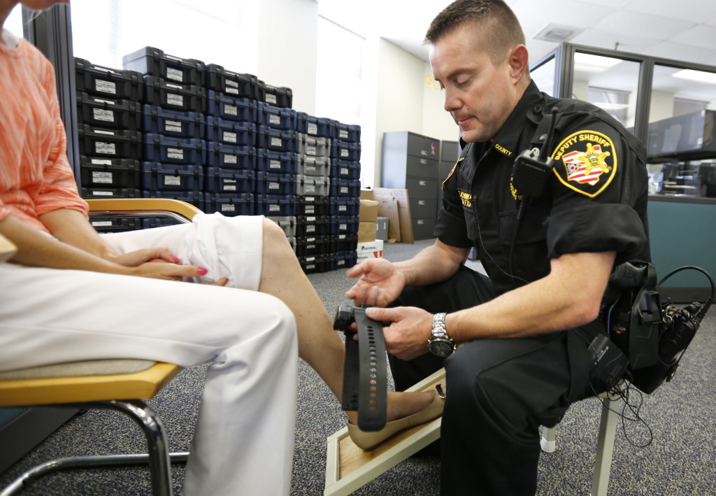 Deputy Edward Sal Attaches An Electronic Monitoring Unit To A Woman Who Was Sentenced Home