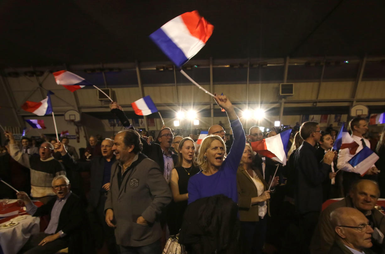 Supporters of Marion Marechal-Le Pen, far right National Front party regional leader for southeastern France, wave flags Sunday at a meeting after the results of the first round of the regional elections, in Carpentras, southern France.