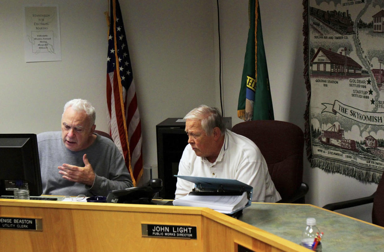 Gold Bar Mayor Joe Beavers, left, and retired resident and volunteer Harry Oestreich take a conference call with banking experts Monday as they try to figure out the next step for the town, which has major financial problems.