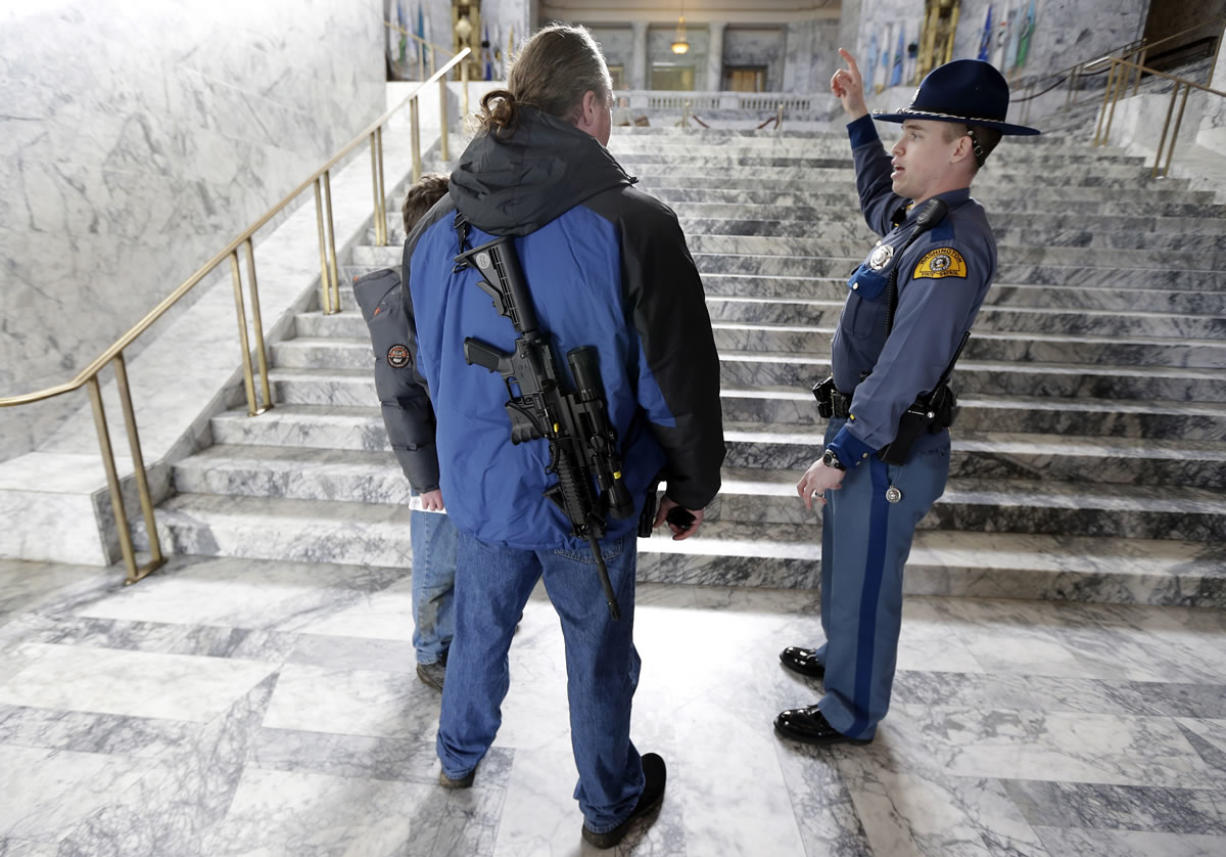 Wearing an AR-15 rifle, Tim Hanrahen, left, of Snohomish, Wash., gets information on the location of legislative offices from Washington State Patrol trooper Todd Israel, right, after Hanrahen attended a gun rights rally Friday at the Capitol in Olympia.