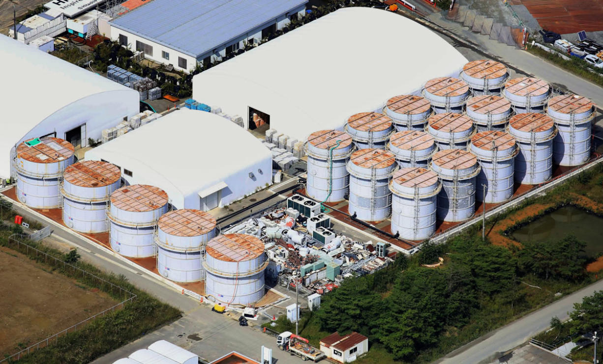 This aerial photo shows the storage tank, fifth from left at left plot, which workers detected the water dripping from the top, at the Fukushima Dai-ichi nuclear plant at Okuma town in Fukushima prefecture, northeastern Japan Thursday, Oct. 3, 2013.  Japan's crippled nuclear plant has a new leak of highly radioactive water entering the Pacific Ocean after a storage tank overflowed. (AP Photo/Kyodo News) JAPAN OUT, MANDATORY CREDIT