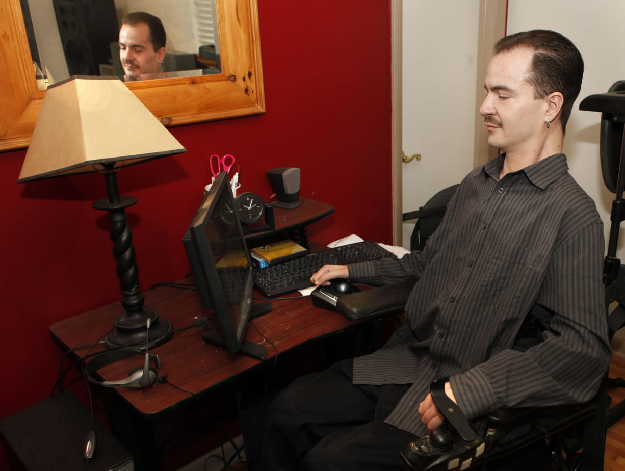 Brandon Coats works on his computer at his home in Denver on Thursday. Coats' Colorado case is giving employers pause. Coats, 33, was a telephone operator for Dish Network. Paralyzed as a teenager in a car crash, he's also been a medical marijuana patient in Colorado since 2009.