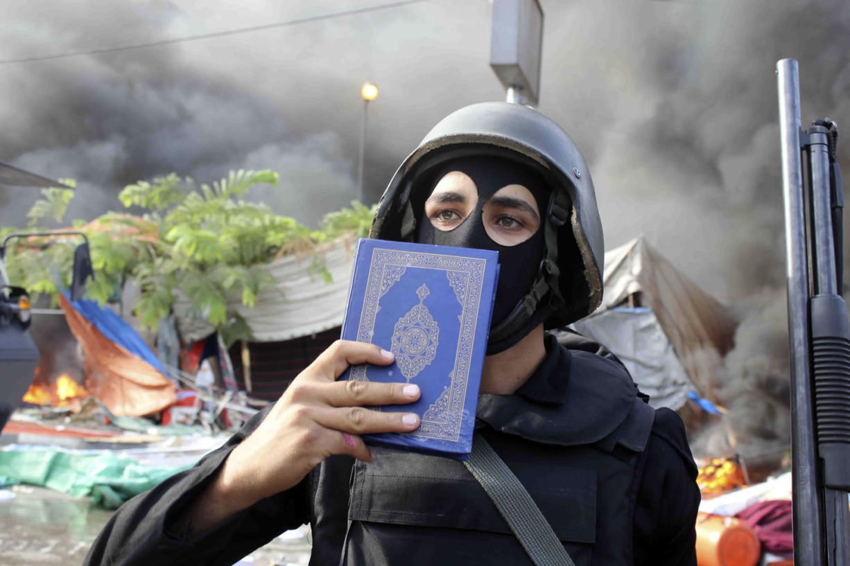 A member of the Egyptian security forces holds up a copy of the Quran as they clear the smaller of the two sit-ins by supporters of ousted Islamist President Mohammed Morsi, near the Cairo University campus in Giza, Cairo, Egypt, on Wednesday.