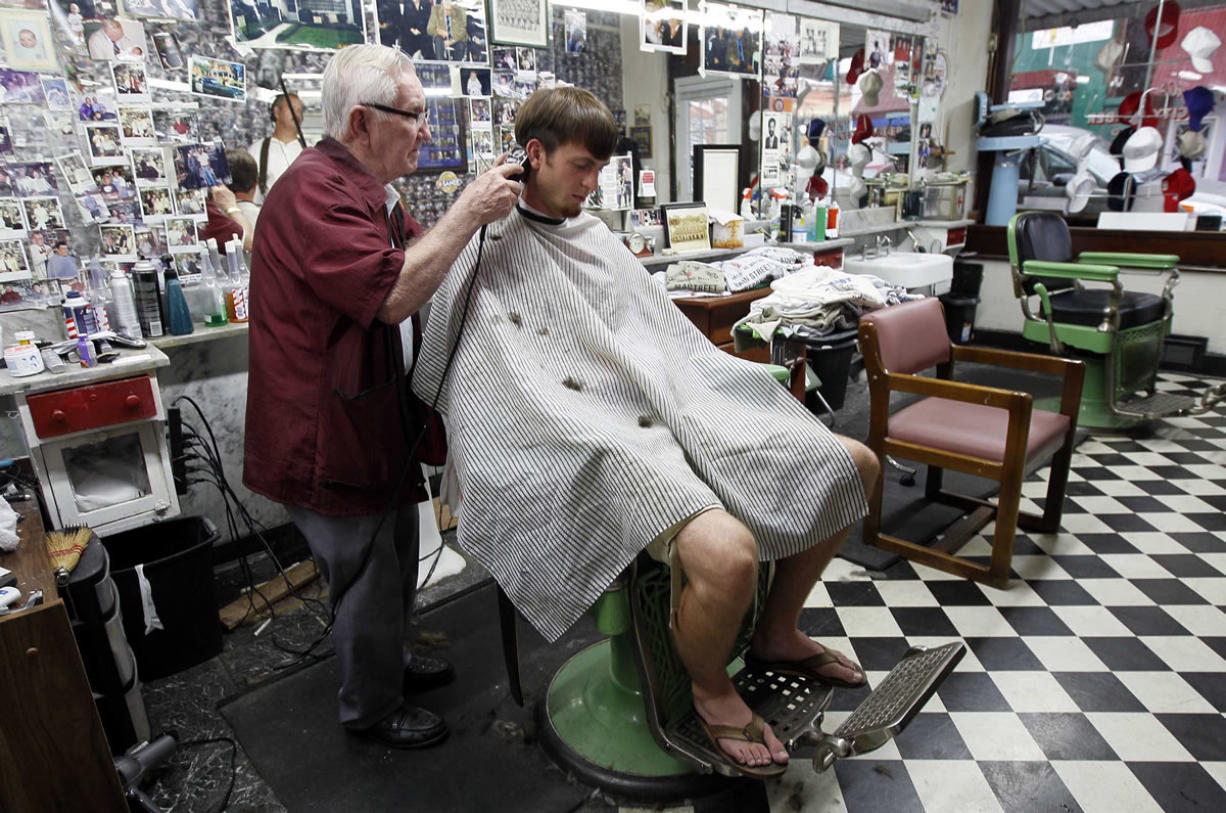 Barber Russell Hiatt, known locally as Floyd, cuts Ethan Boles' hair at Floyd's City Barber Shop in Mount Airy, N.C.