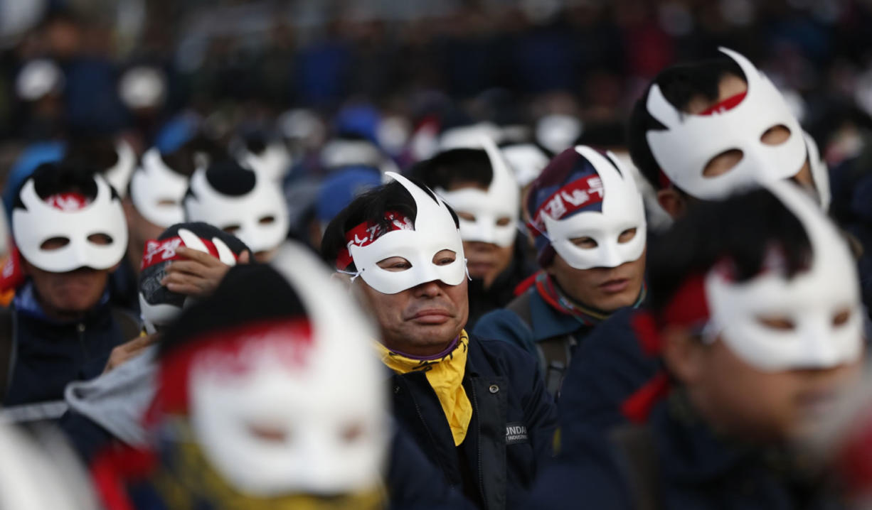 Masked protesters attend an anti-government rally Saturday in downtown Seoul, South Korea.
