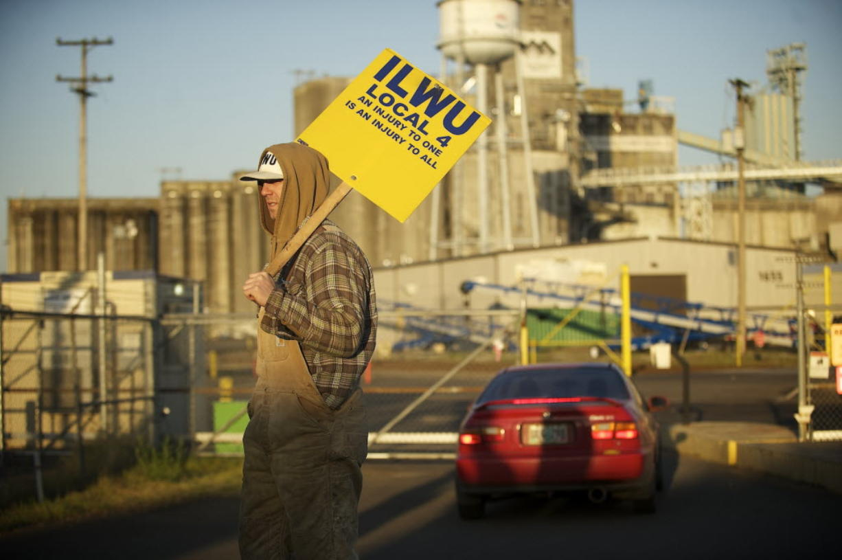 An International Longshore and Warehouse Union local 4 supporter holds a sign outside the main gate to United Grain as a vehicle enters May 1 in Vancouver. The Clark County Prosecuting Attorney's Office won't file charges against a longshore worker accused of sabotaging operations at United Grain Corp.