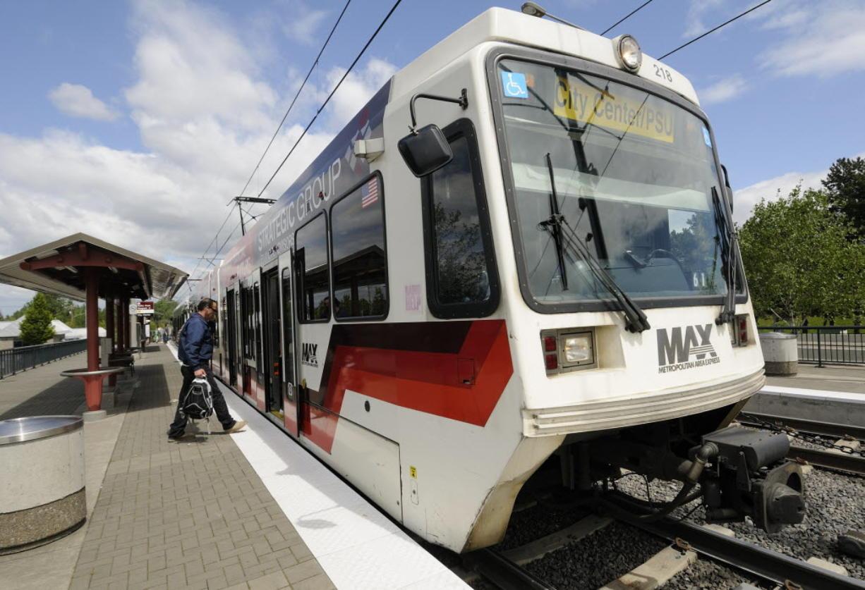Passengers board a TriMet Max light rail train at the Delta Park/Vanport light rail transit station.