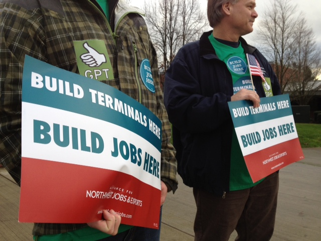 BNSF employee Tim Falsetto, right, joins pro-coal activists Wednesday in advance of a public hearing at Clark College on a proposed coal export facility near Bellingham.