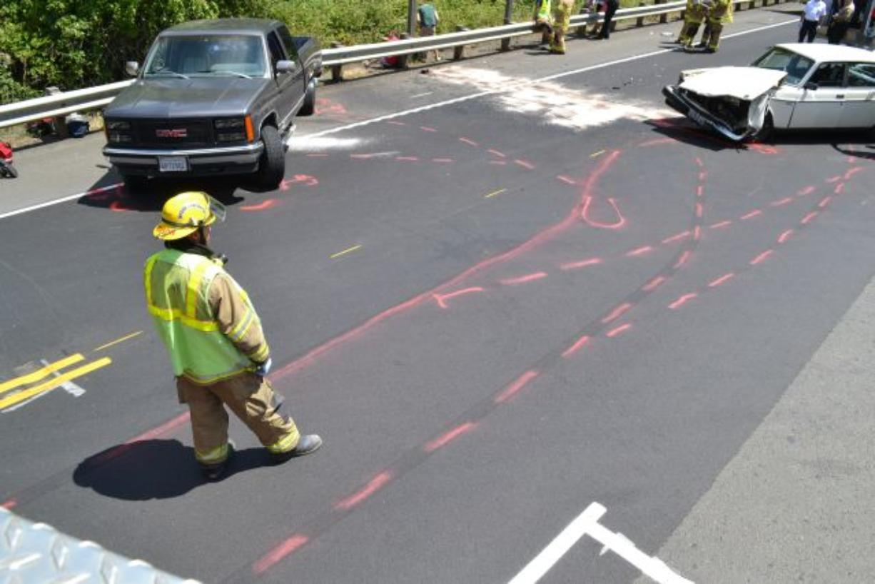 A firefighter surveys the scene of an injury crash that resulted in injuries to six people, including at least one from Vancouver.