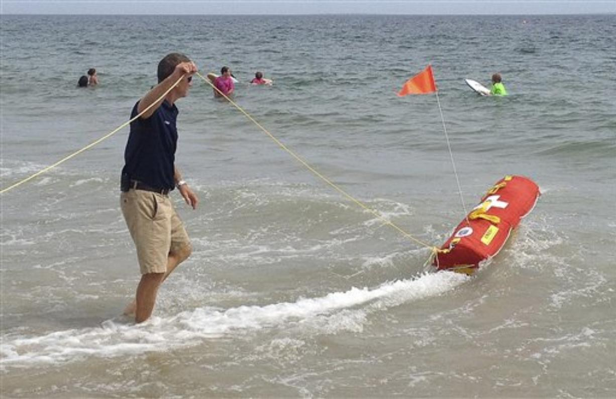 In this Wednesday, Aug, 8, 2012 photo, Misquamicut, R.I., Fire Chief Louis Misto, left, holds a line attached to the EMILY remote-control lifesaving device as it propels itself in the water and away from the shore at Old Town Beach, in Westerly, R.I.