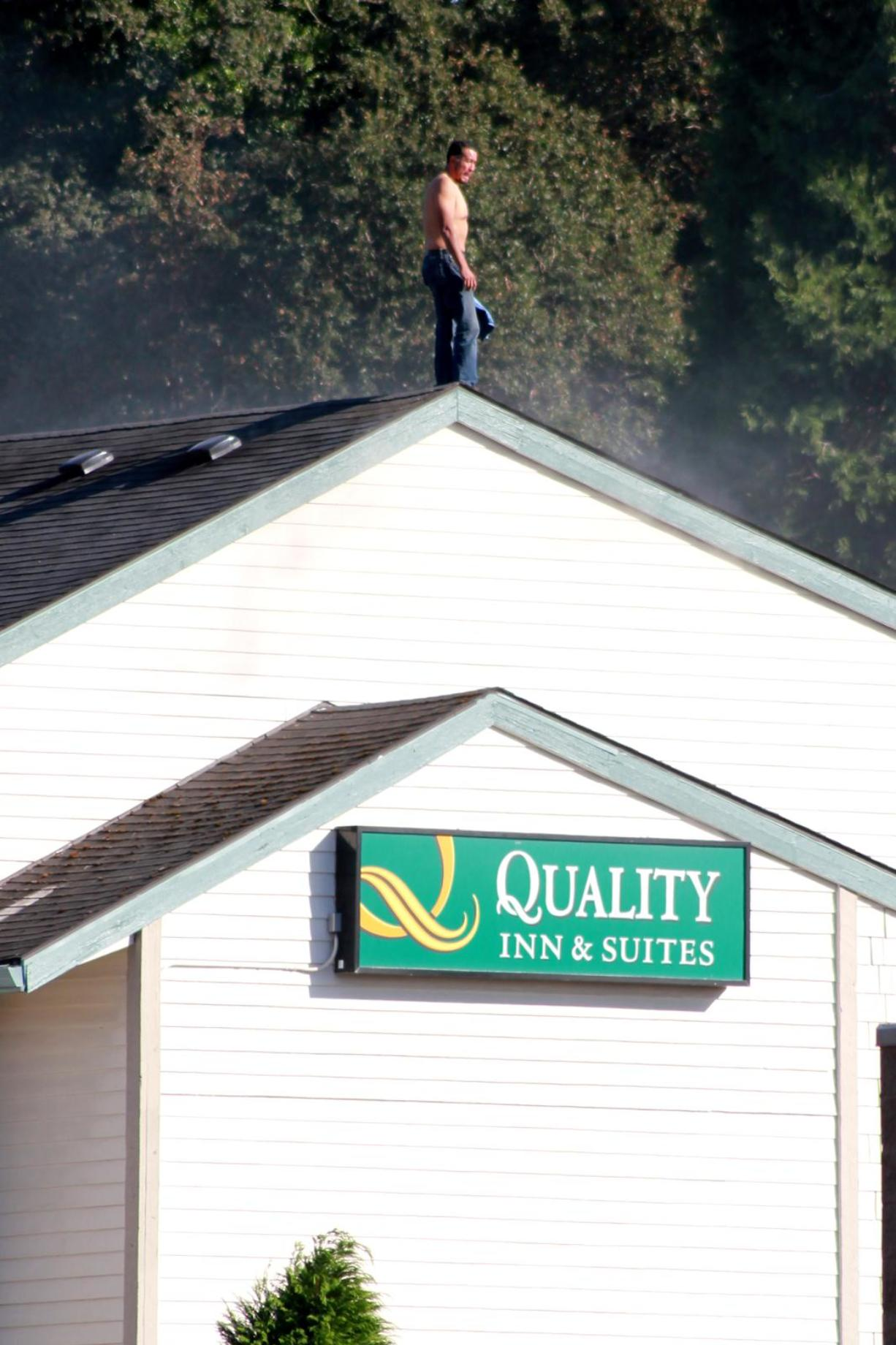 A man stands atop a smoldering hotel in Hazel Dell on Saturday. The man pushed away ladders set up by firefighters to rescue him.