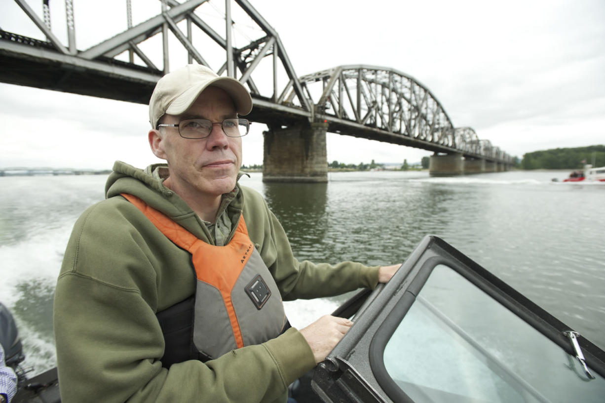 Environmental activist Bill McKibben passes under the Vancouver Railroad Bridge during a boat tour of  the Columbia River and the crude oil site proposed for the Port of Vancouver on Wednesday.