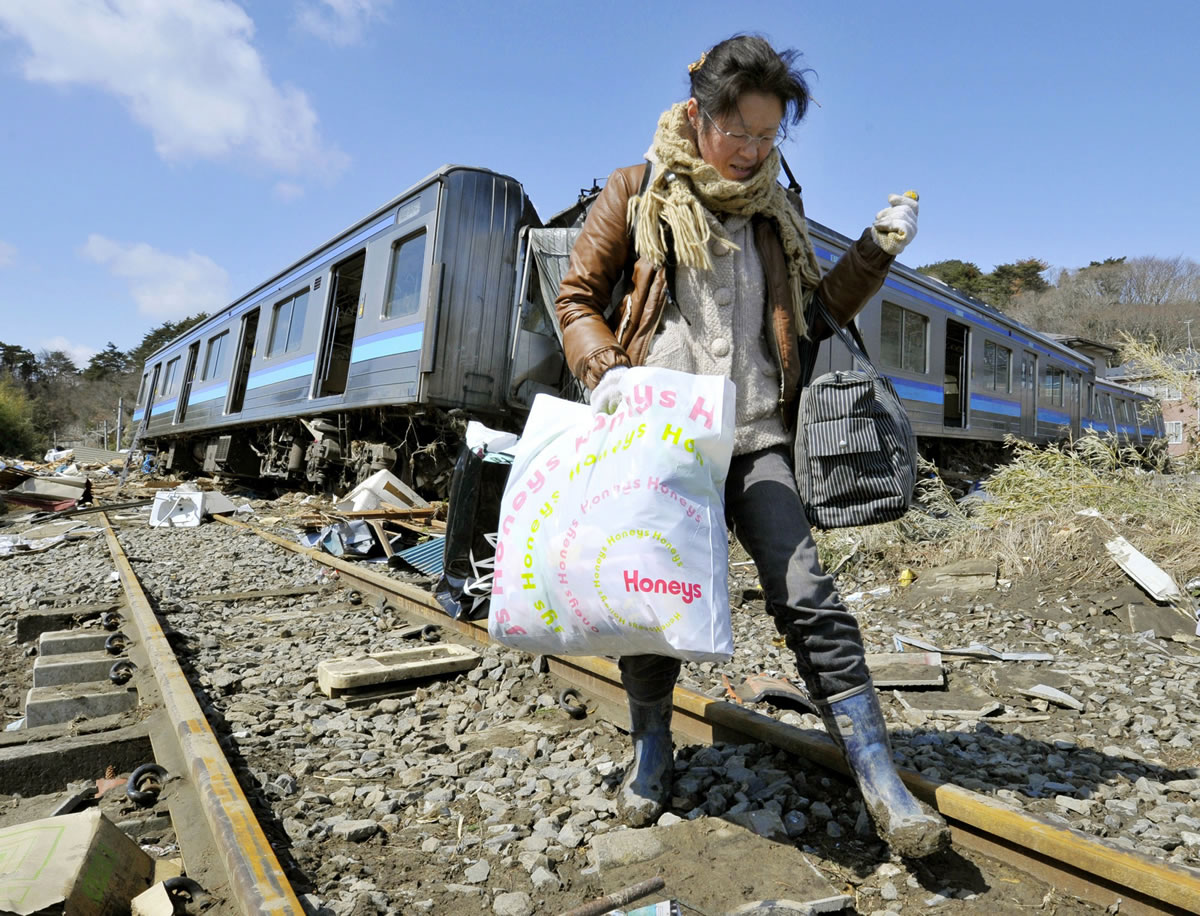 Kyodo News files A woman walks along a railroad track, passing tsunami-wrecked train cars in Higashimatsushima, Miyagi Prefecture, Japan, after the 9.0 earthquake and tsunami devastated that region in 2011. The Pacific Northwest could see similar damage if the Cascadia fault ruptures.