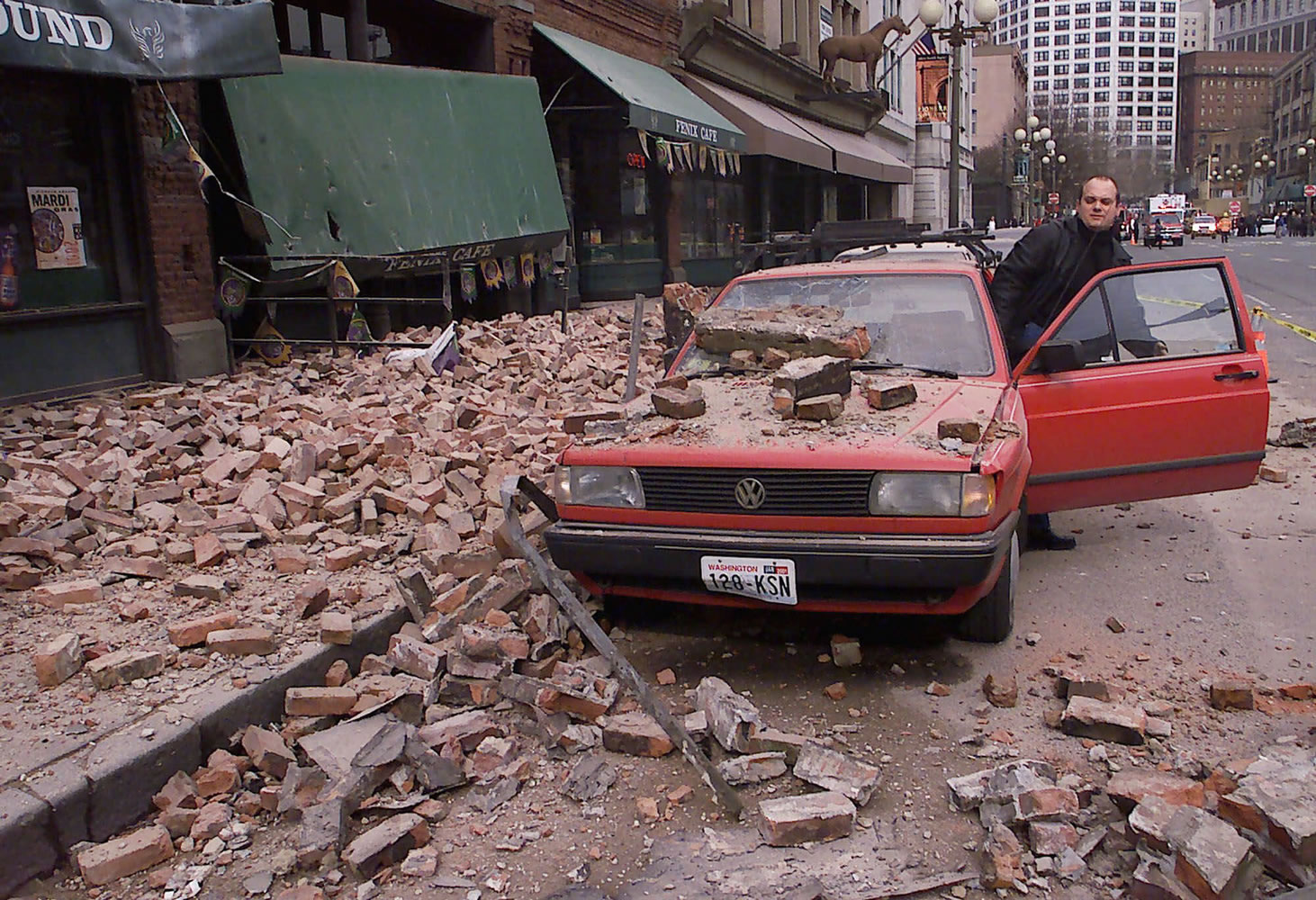 FILES/Associated Paul Riek checks to see if his car starts after debris fell on it from the top half of a nearby building during the 2001 Nisqually earthquake in Seattle. The 6.8 earthquake caused extensive damage, but earthquakes of that size are not uncommon in the Pacific Northwest.