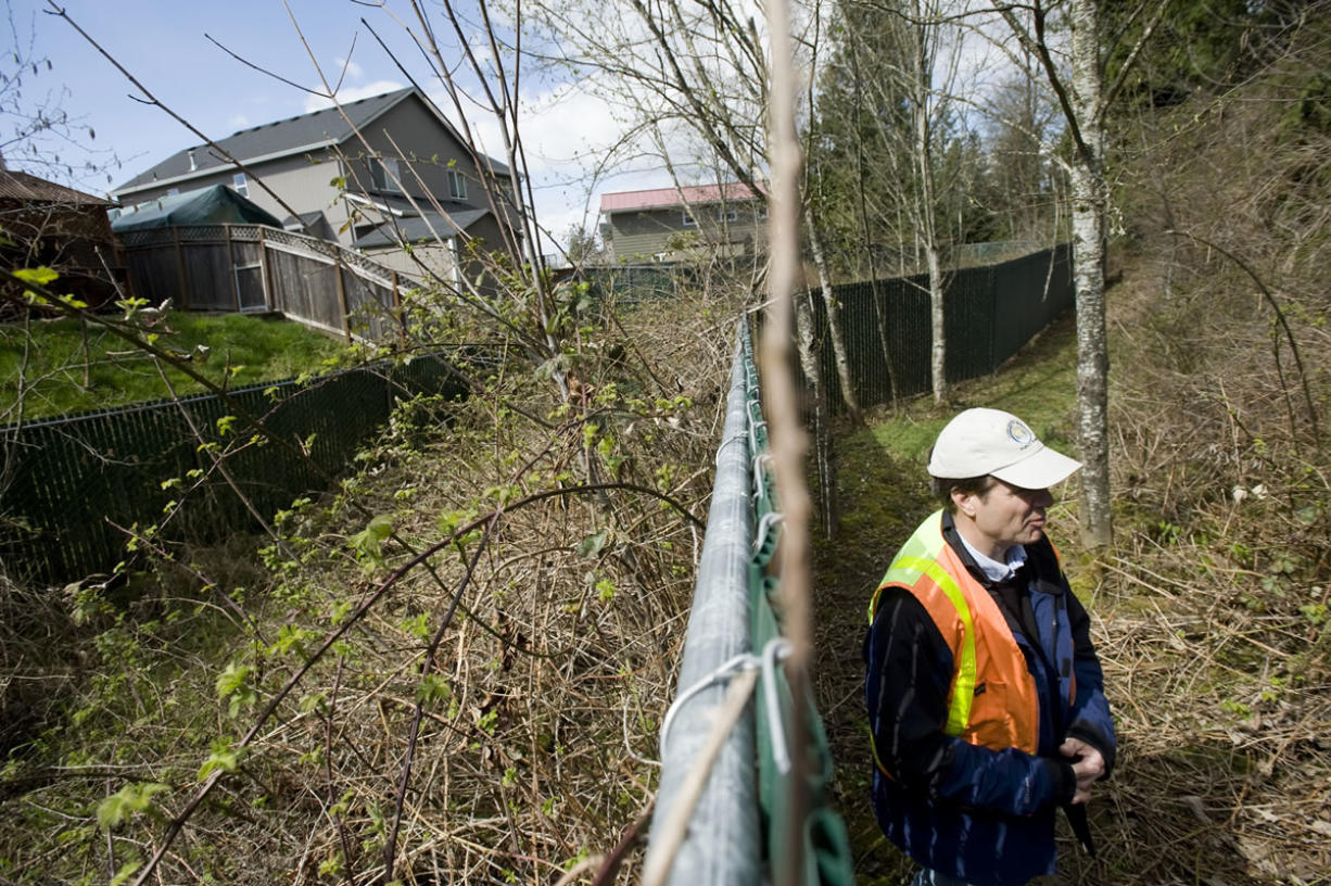 Cary Armstrong, source control specialist with the Clark County Department of Environmental Services, points out a poorly maintained stormwater site in a Vancouver neighborhood in 2011.