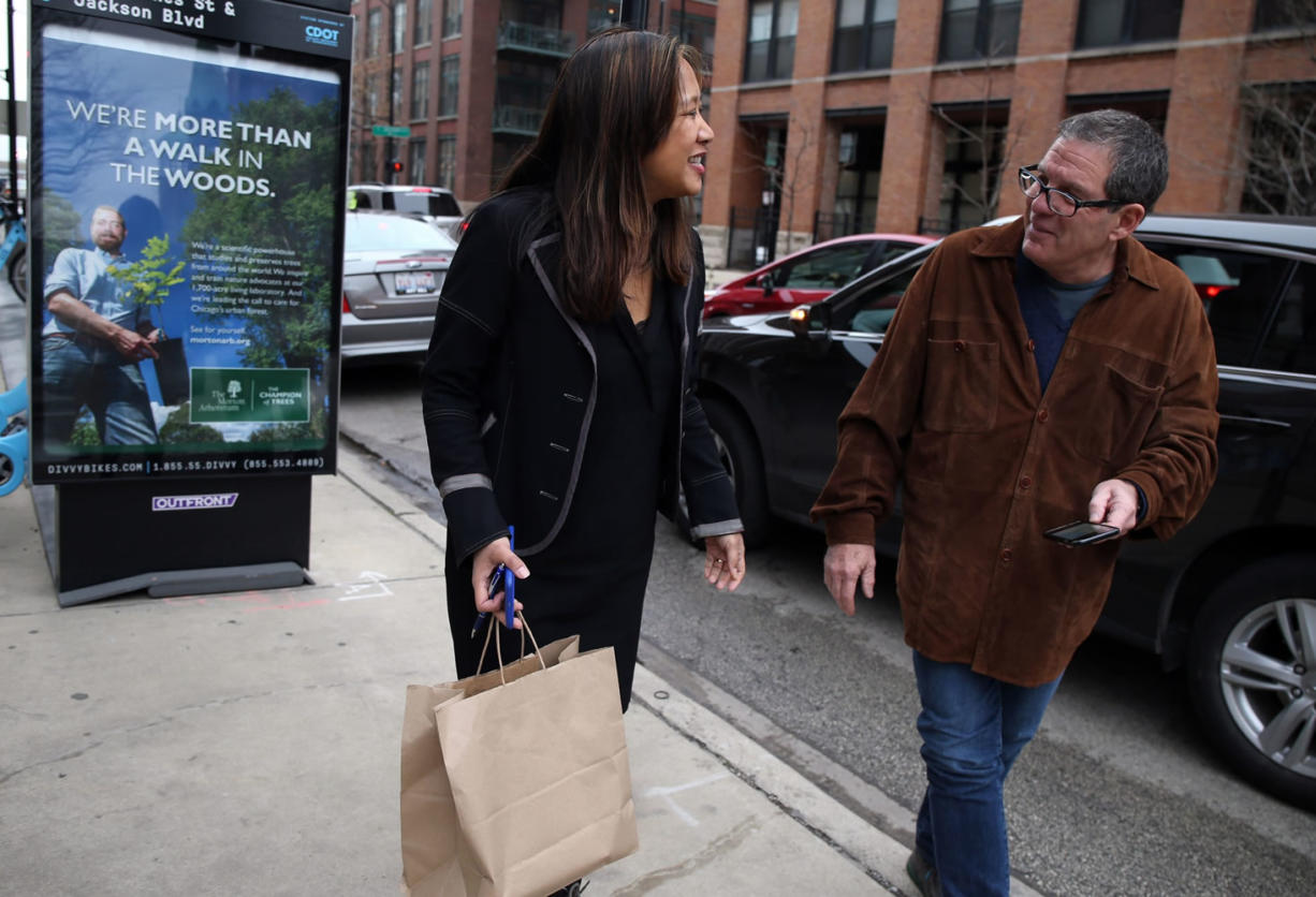 Maria Kim thanks UberEats driver Jim Butler for delivering her lunch in Chicago on Dec. 22. (Terrence Antonio James/Chicago Tribune)