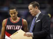Portland Trail Blazers guard C.J. McCollum (3) watches as head coach Terry Stotts draws a play in the second half of an NBA basketball game against the Washington Wizards, Monday, Jan. 18, 2016, in Washington. The Trail Blazers won 108-98.