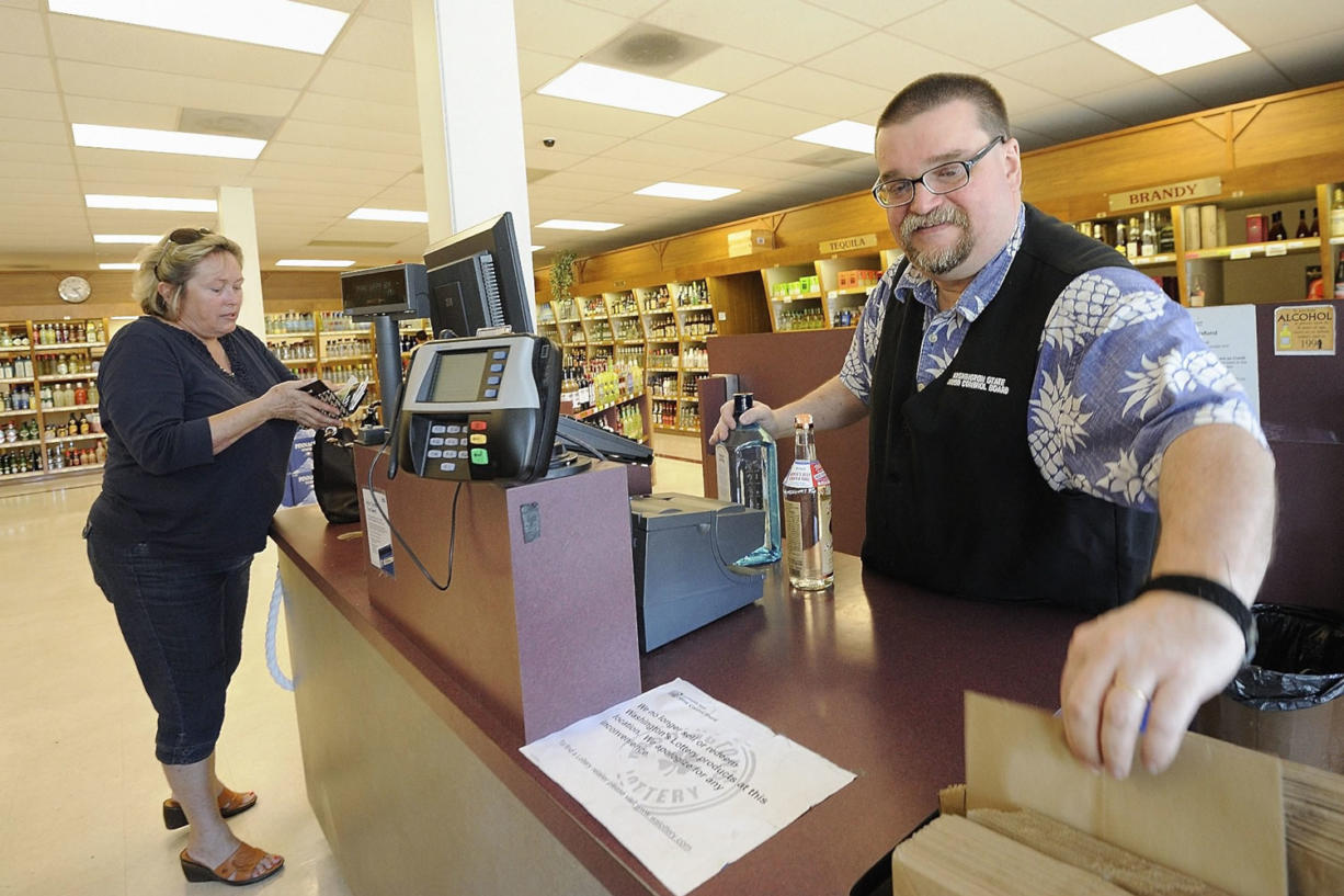 Liquor store employee Eric Simonson helps customer Andrea Gecho on Monday at the state-owned liquor store at 1700 Main St. in Vancouver. Tony Singh of Terre Haute, Ind., was high bidder at $150,000 in a state auction to purchase the store.