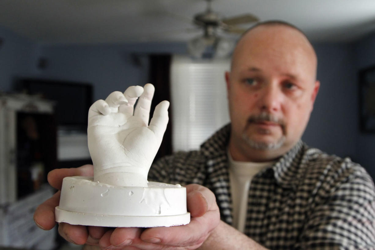 In this January photo, former Clark County Sheriff's Deputy Ed Owens holds a plaster hand casting taken from his son Ryan at the hospital shortly after his 2010 death from an accidental shooting.