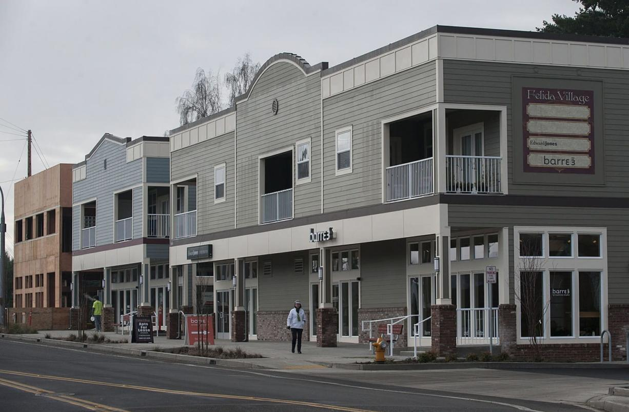 A pedestrian walks past buildings Felida Village, the new development project which includes a mix of commercial and residential space at the corner of Northwest 119th Street and 36th Avenue. Developer Ron Edwards, who lives five blocks from the new buildings, said he hopes the project becomes a gathering place for the community. (Amanda Cowan/The Columbian)