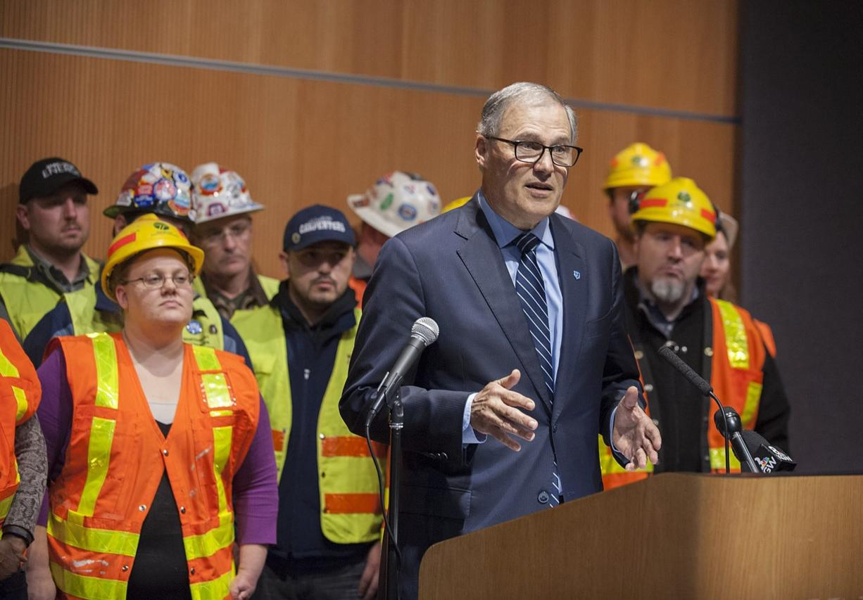 Democratic Gov. Jay Inslee, foreground, speaks to the crowd and the media Wednesday afternoon at the Vancouver Community Library.