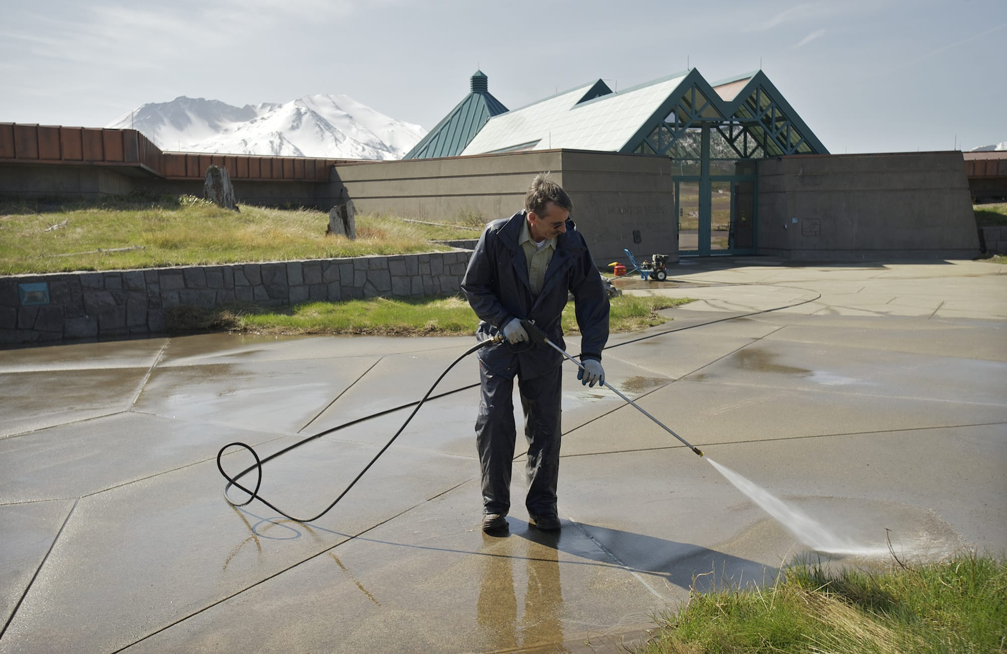 Roger Sadler of the U.S. Forest Service washes a walkway Friday outside the Mount St. Helens Science and Learning Center at Coldwater.
