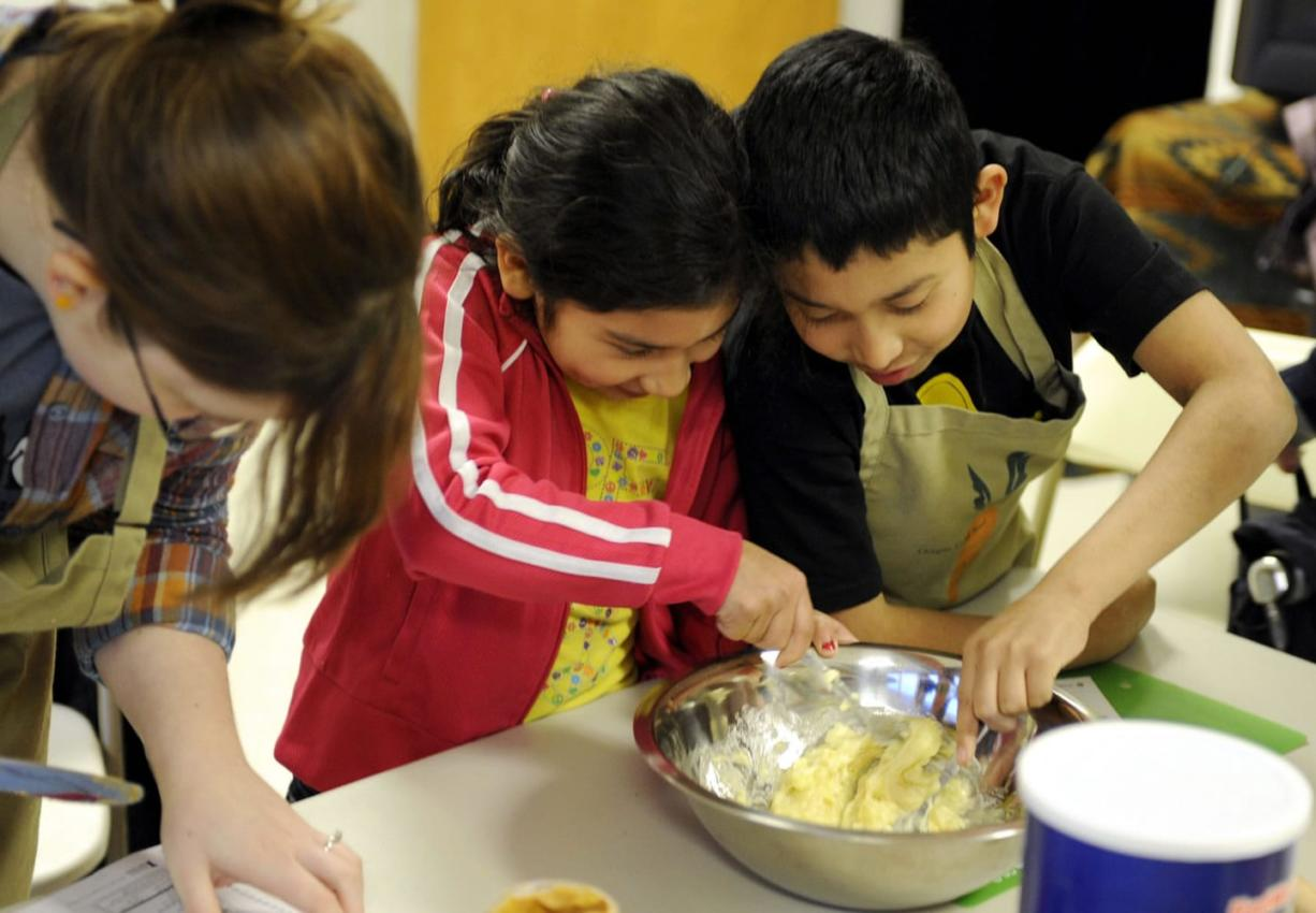 Seudy Bolon and her brother Alexander Bolon Manrero, right, mix dough for oatmeal cookies during a nutrition education class offered by a Vancouver food pantry.