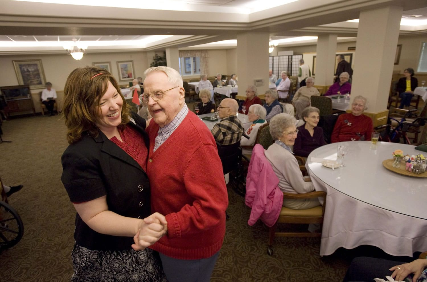 Resident Larry Hayden, 89, dances with activities director Michelle Avdienko during a wine and cheese social hour at Glenwood Place Senior Living on Friday.
