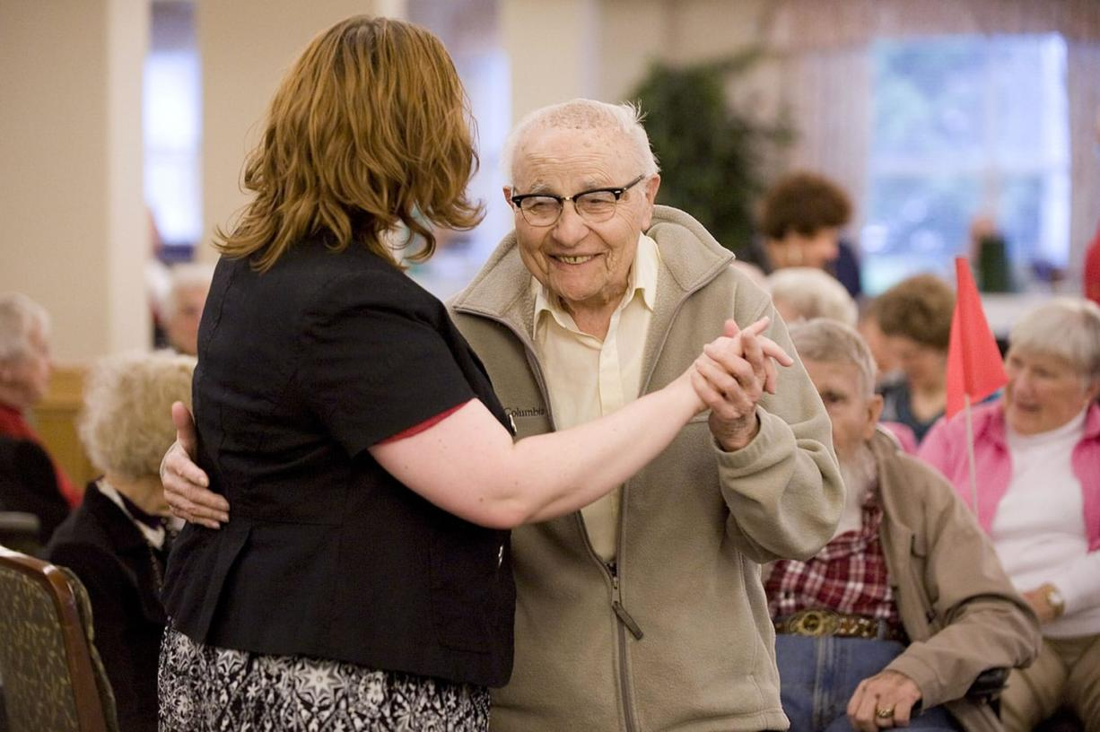 Resident Rocky Cortese, 94, dances with activities director Michelle Avdienko during a wine and cheese social hour at Vancouver's Glenwood Place Senior Living. Research suggests older people are happier than younger ones.