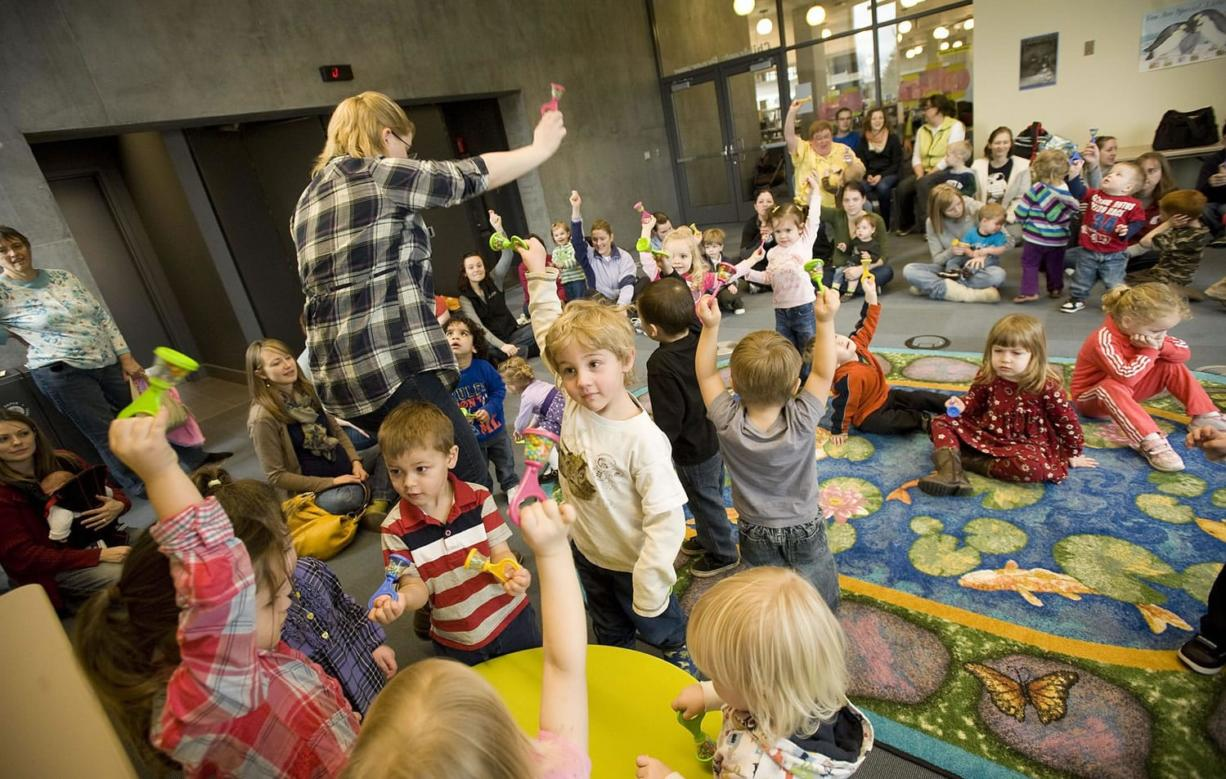 Kids shake rattles as children's librarian Kendra Jones leads them in song during Tuesday's toddler story time at the Vancouver Community Library.