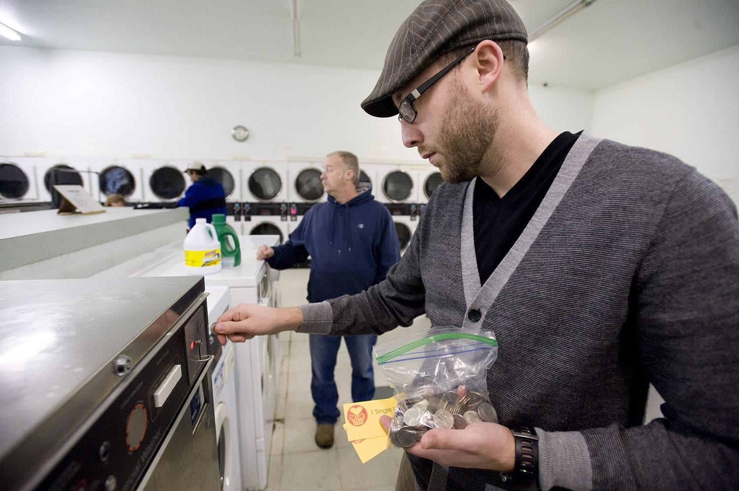 Jason Twyman, an elder at Camas Friends Church, feeds quarters into a machine at Riverside Laundry.  The church's Laundry Love program helps needy people wash their clothes.