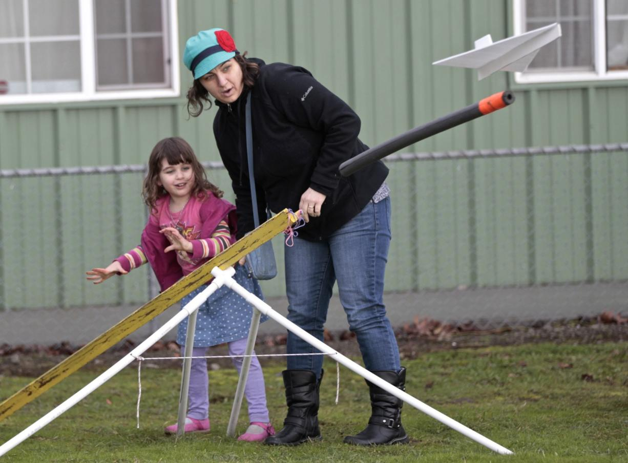 Vivian Larson, 4, and Danielle Galipeau (mom) of Portland launch a glider at the Pearson Field Education Center. The center hosted a day of flight simulation and model-glider building for kids. (Photos by Steve Dipaola for the Columbian)