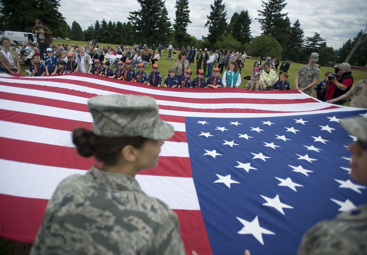 Prairie High School Air Force Junior ROTC cadets and local scouts hold up a large American flag Tuesday during the annual Flag Day celebration at the Vancouver Barracks parade ground.