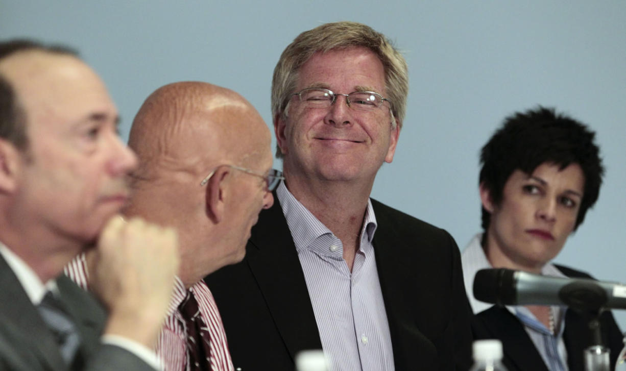 Travel guide Rick Steves, second from right, smiles as he sits with Mark Johnson, from left, Dr. Robert Wood and Alison Holcomb during a Seattle news conference Wednesday announcing the filing of an initiative to legalize possession of marijuana in Washington.