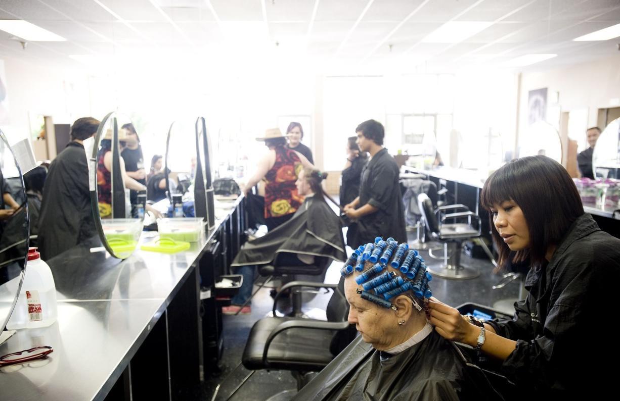 Manning Academy student Joy Toburen styles Mary Sellers' hair.