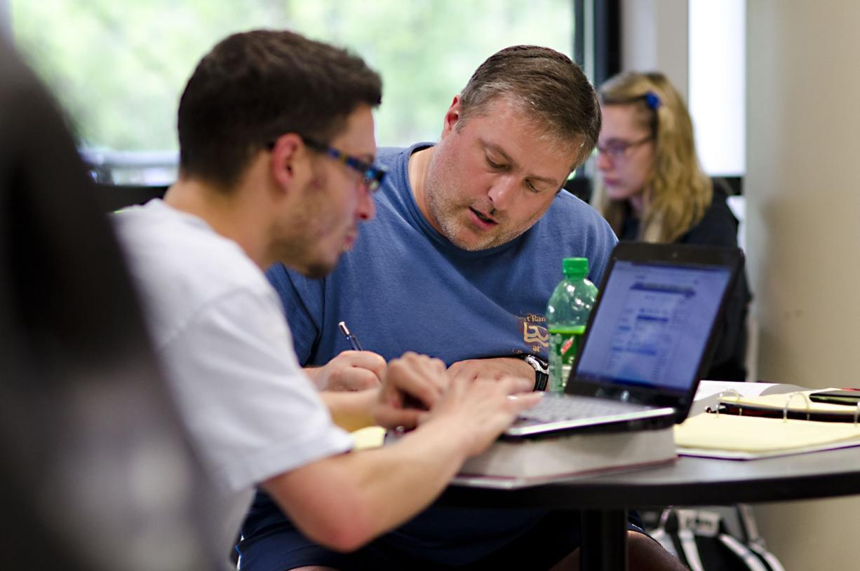 Steven Doerk, center, works on homework with his classmate, Zach Martinez, before their math class at Clark College. Doerk, laid off in November, is taking classes to bolster his chances of landing a full-time job.