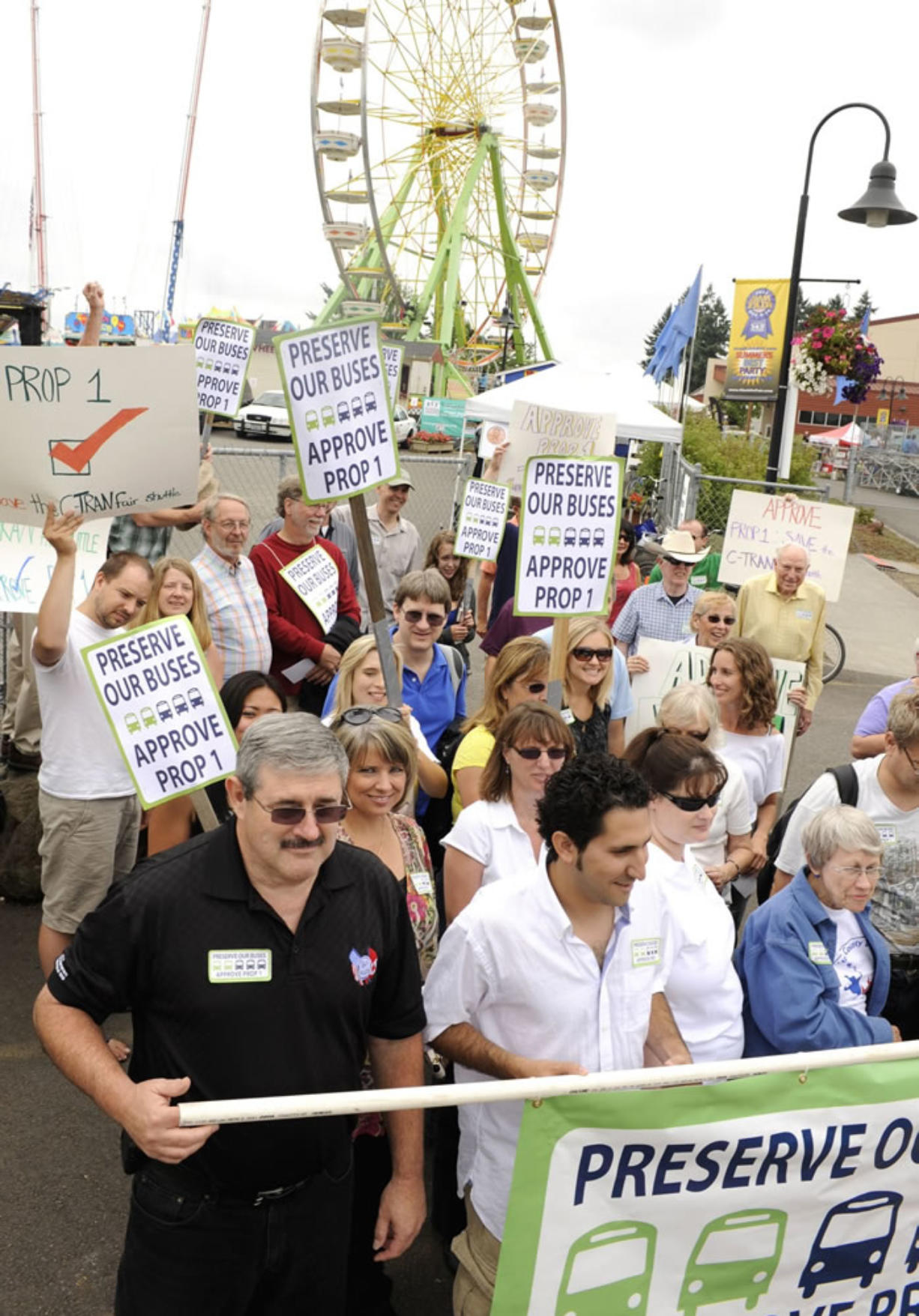 Supporters of Proposition 1, including Roy Jennings, bottom left, of the Amalgamated Transit Union 757, rally for C-Tran's sales tax increase outside the east entrance to the Clark County Fair on Saturday.