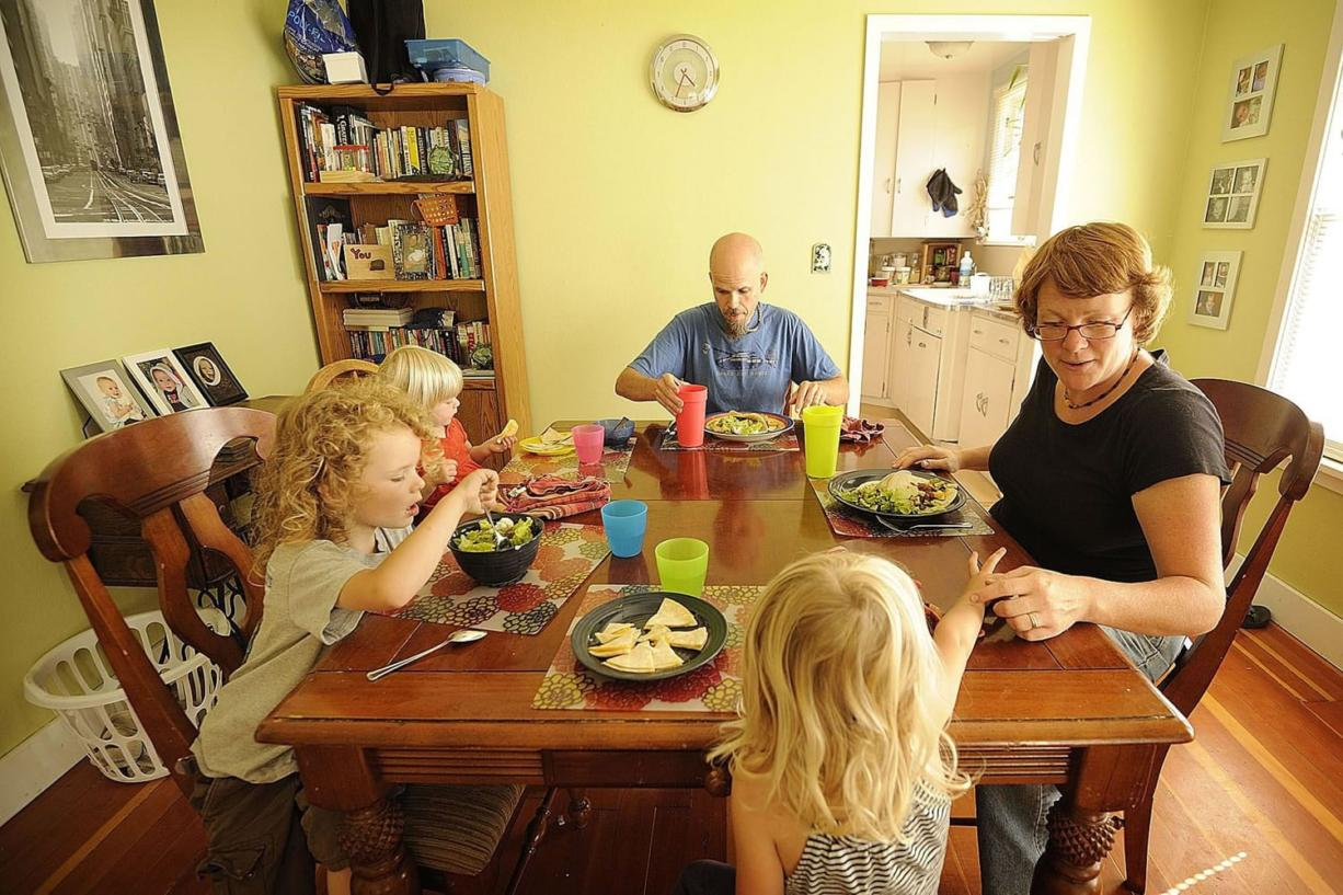 The Cowen family, clockwise from top center, Eric, Eileen, Marley, 3, Abraham, 4, and Bridget, 1, eat a dinner of red beans, tortillas and fresh vegetables at their Vancouver home.